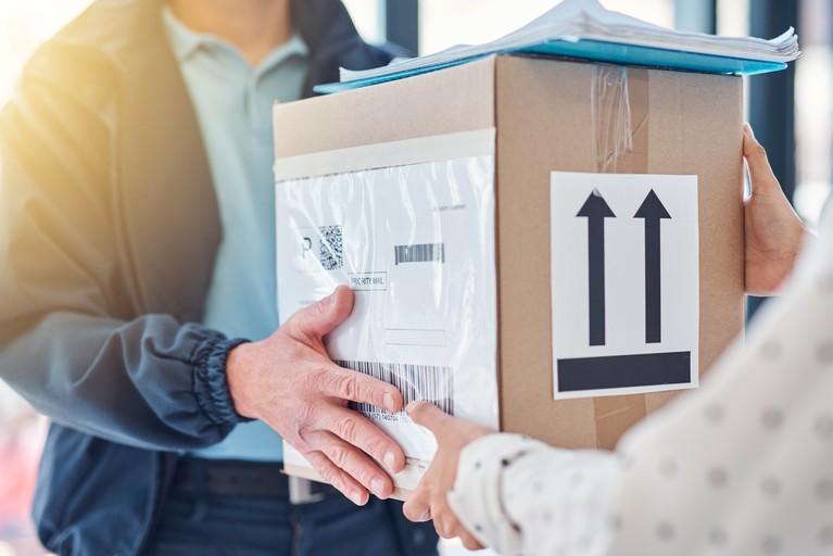 Ein Mann übergibt ein Paket an eine Frau