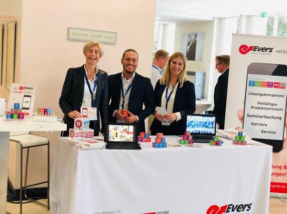 Drei Mitarbeiter der Evers GmbH lächeln freundlich an ihrem Messestand