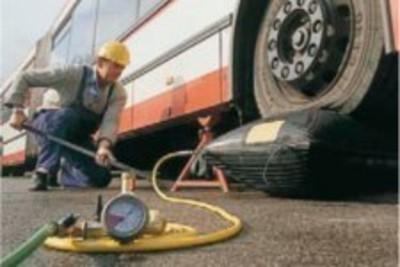 Eine Hebekissen wird unter dem Reifen eines Busses aufgepumpt und der Bus somit gehoben. Ein Mann mit Helm hält eine Stange und führt sie unter den Bus.