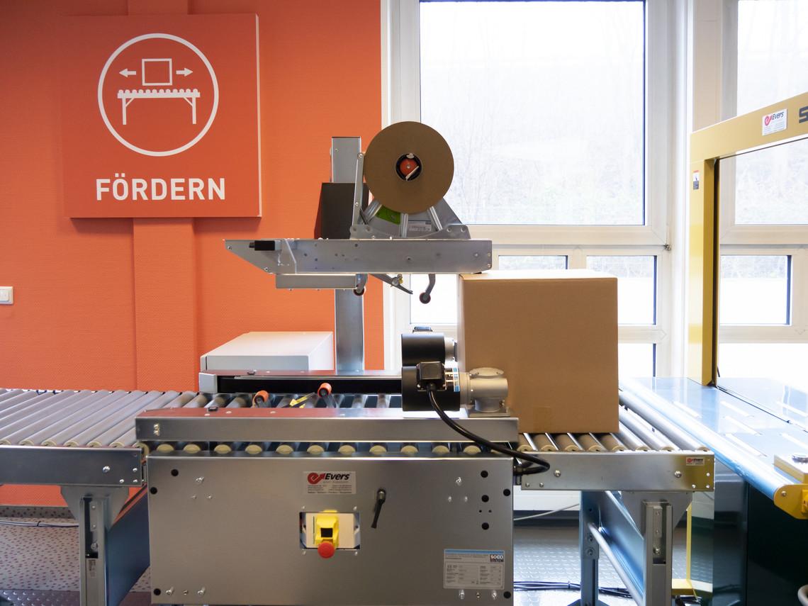 Kartonverschließmaschine verschließt Karton mit reinem Papierklebeband.
