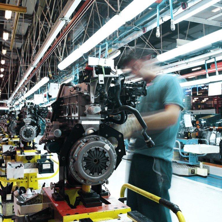 Ein Mann befindet sich bei der Konstruktion eines PKW-Motors