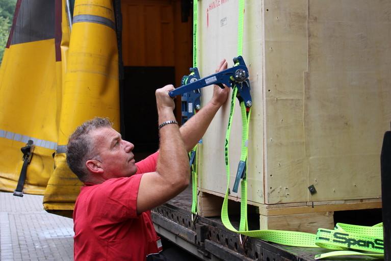 Ein Evers-Mitarbeiter spannt Zurrgurte an einer Palette innerhalb eines LKWs