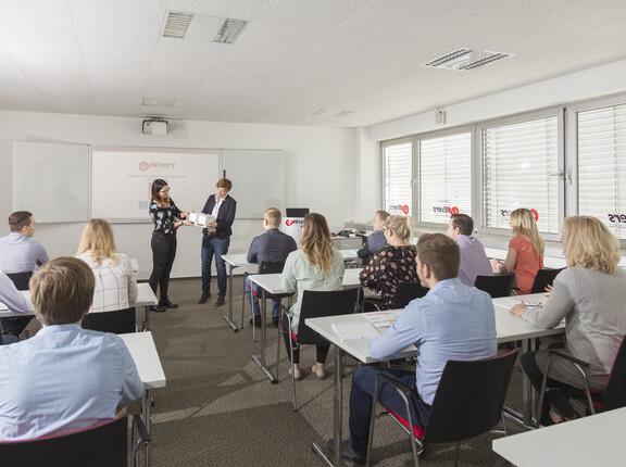 Zwei Fachdozentinnen erklären Ladeeinheitensicherung auf der Palette vor Seminargruppe