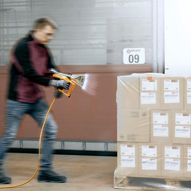 Ein Mann bildet eine Ladeeinheit, indem er eine mit Paketen beladene Palette mit Schrumpffolie verschließt