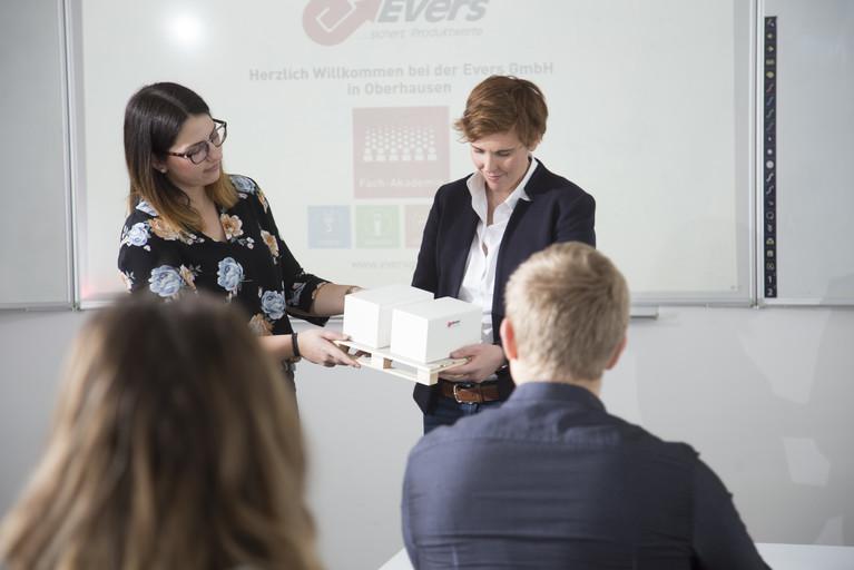 Zwei Mitarbeiterinnen der Evers GmbH halten ein Seminar und zeigen eine Miniaturversion einer optimal gesicherten Palette