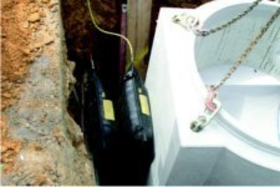 Zwei Hebekissen werden in einen Graben zwischen der Wand und einem Betonbauteil aufgepumpt