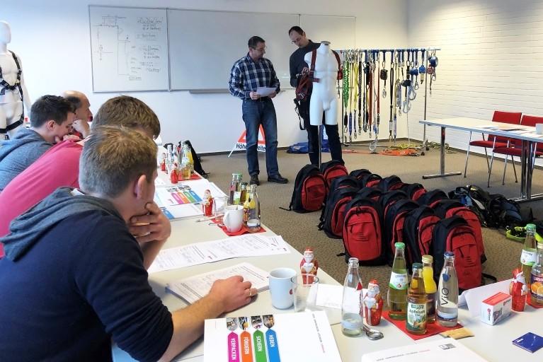 In der Fachakademie zeigt ein Dozent mehreren Teilnehmern, anhand eines Dummys, wie man einen Auffanggurt richtig anlegt