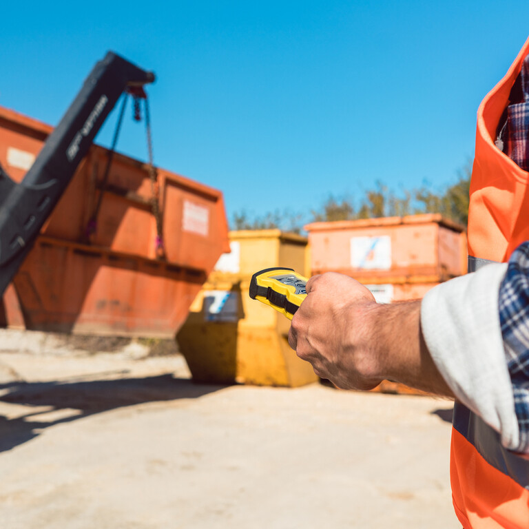 Ein Absetzkippfahrzeug befindet sich auf einer Baustelle und entlädt seinen Container