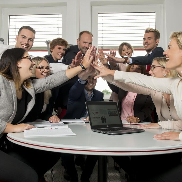 Mitarbeiter der Evers GmbH sitzen an einem runden Tisch und schlagen zusammen ein